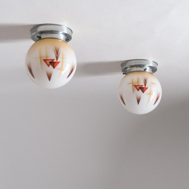 Pair of small Art Deco ceiling or wall lights, circa 1930. Blown glass diffuser with enameled geometric decorations. Nice original condition with minor patina. One original nickeled and ceramic E27 socket each with new wiring.