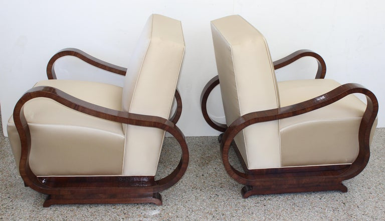This stylish set of Art Deco style lounge chairs are attributed to the Czech designer Jindřich Halabala and they date to the 1930s. The frames are a deep walnut coloration, and the upholstery is a soft gold satin.  Note: We're not certain if the