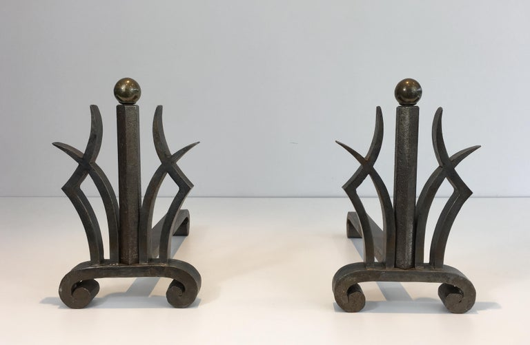 This pair of Art Deco hammered wrought iron and brass andirons is in the style of famous wrought iron maker Raymond Subes. They are French, from the 1930s.
