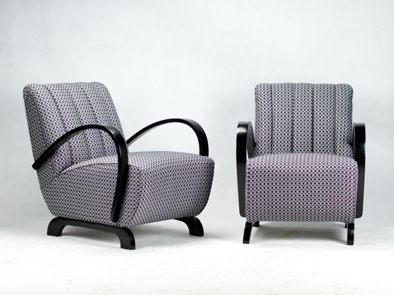 This lounge chairs were designed by Jindrich Halabala and produced in former Czechoslovakia in the 1930s by UP Zavody Brno. The chairs have curved armrests and legs made from stained beech in black French polish finish and new upholstery.