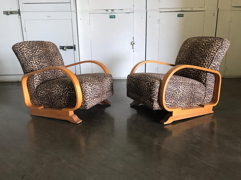A handsome pair of lounge chairs. Made of wood construction with nice bentwood armrest design, with the original metal springs.  The upholstery appears to have be redone sometime in the late 1980s or 1990s. It's in Fine condition. The wood appears