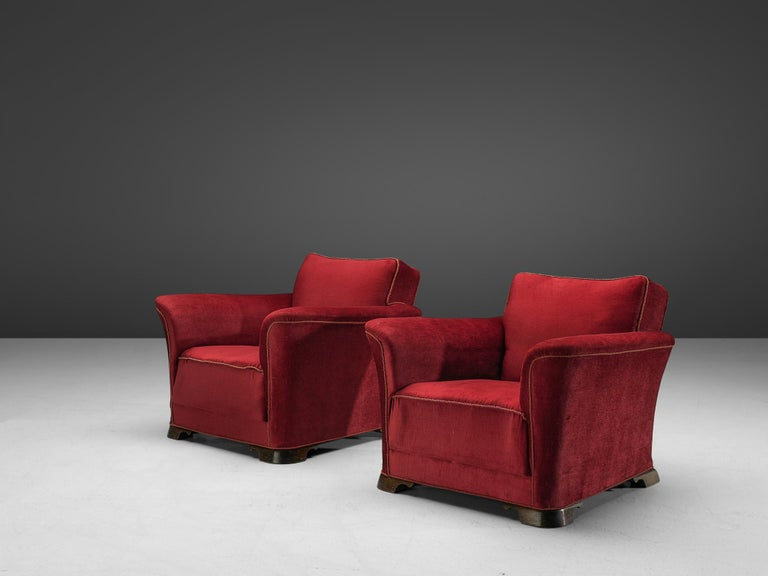 Pair of lounge chairs, velours and mahogany, Denmark, 1940s  A set of two grand and comfortable armchairs in red velours upholstery. The lounge chair features a thick seat, which is characteristic for the Art Deco movement. Large upsweeping armrests