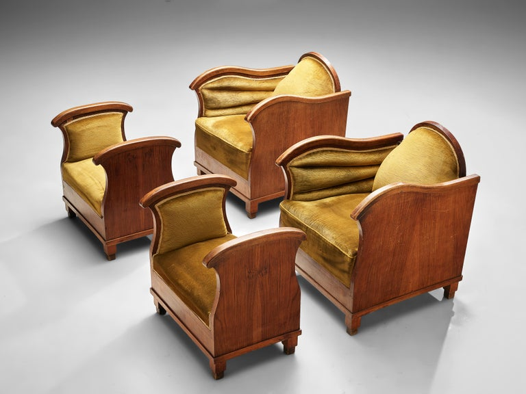 Art Deco lounge chairs, wood, moss green velvet, Europe, 1930s  Set of two Art Deco armchairs with accompanying ottomans upholstered in moss green velour. The comfortable chairs have a laidback backrest and wavy armrests, emphasized by the detailing