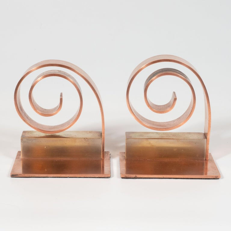 This elegant pair of Art Deco machine age scroll form bookends were designed by the celebrated luminary Walter Von Nessen and realized in the United States, circa 1950. With their clean lines and dynamic form, these bookends would be a winning