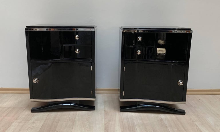 Pair of very elegant Art Deco nightstands with curved front, black lacquer and chrome parts.