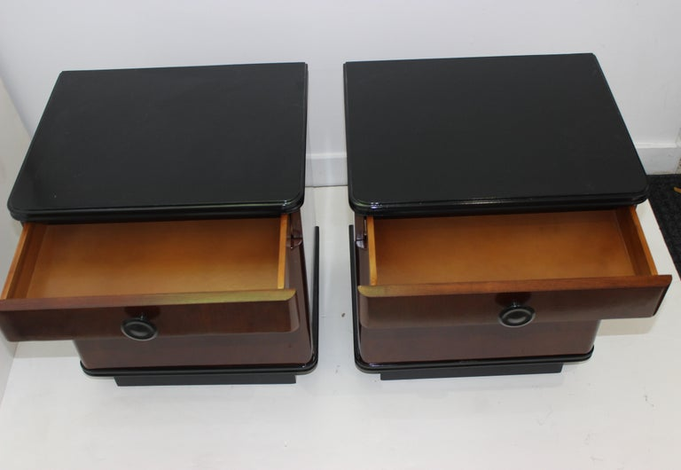 Art Deco nightstands 1930s restored and ebonized, a pair from a Palm Beach estate, recently ebonized tops and recessed feet, iconic curved corners, each has a removable inner shelf and each has a drawer. Elegant size perfect for a favorite