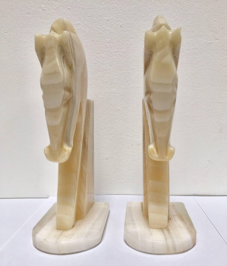 Pair of Art Deco style stylized horses head bookends. Vintage set of bookends, hand-carved in onyx in a shade of ivory and browns. Hermes style horses, great modern design. Measures: Each horse head measure 8.5