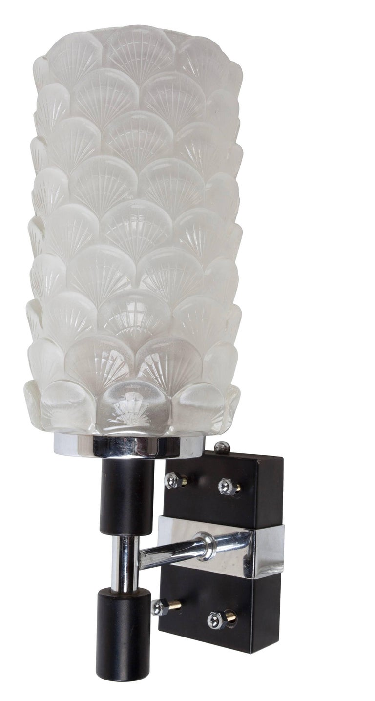A pair of exquisite Art Deco period glass sconce shades with scallop shell motif on chrome and black metal back plates. Rewired for American use, porcelain socket and takes a regular size light bulb. European. As of this writing I have two