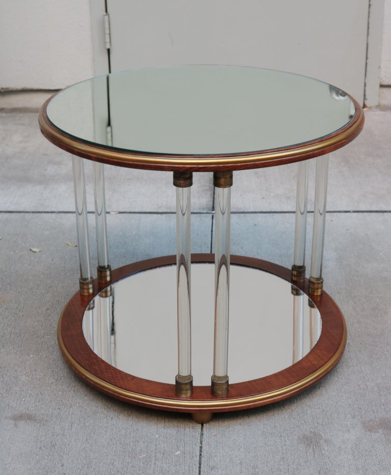 A pair of Art Deco round two-tier side tables. Mahogany with a pair of Art Deco two-tier round side tables. Mahogany with mirror glass tops, glass legs, patinated brass details, giltwood feet and mirrored bottom tier.