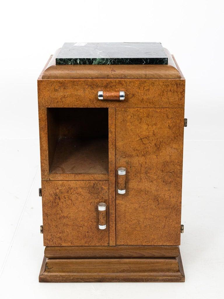 Pair of Art Deco style side table with original green marble tops, circa 1930s. Each table features two cabinets, one cubbyhole shelf, and a single top drawer. Please note of wear consistent with age.