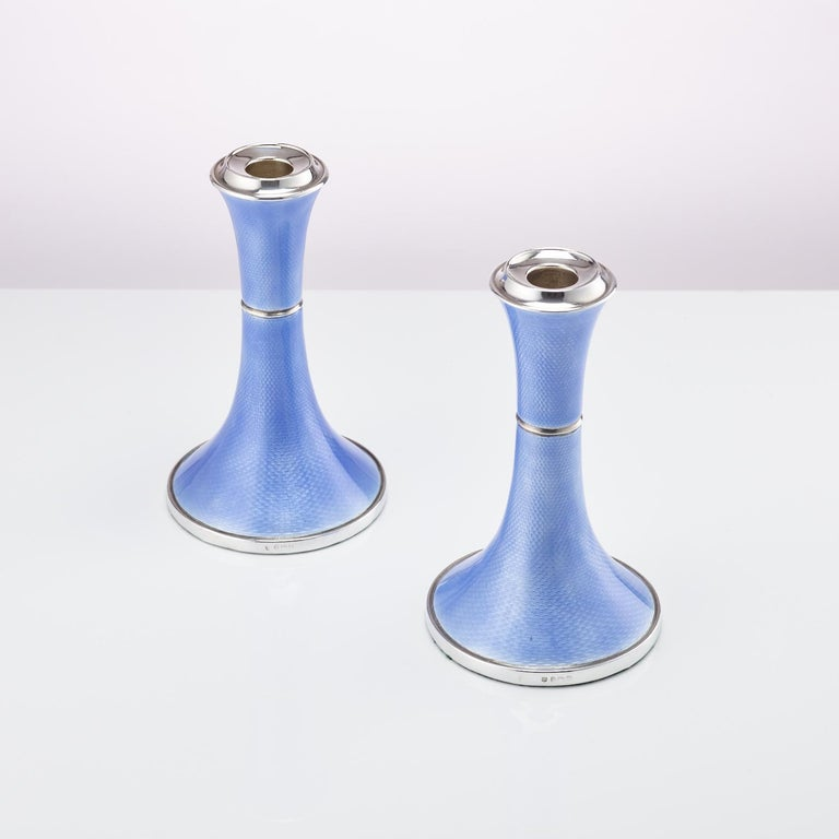 A beautiful pair of Art Deco silver and guilloche enamel candlesticks. The enamel is a stunning blue which flows around the shape of the base up to the top.  They are a good size and very aesthetically pleasing.  Origin: Birmingham, England,