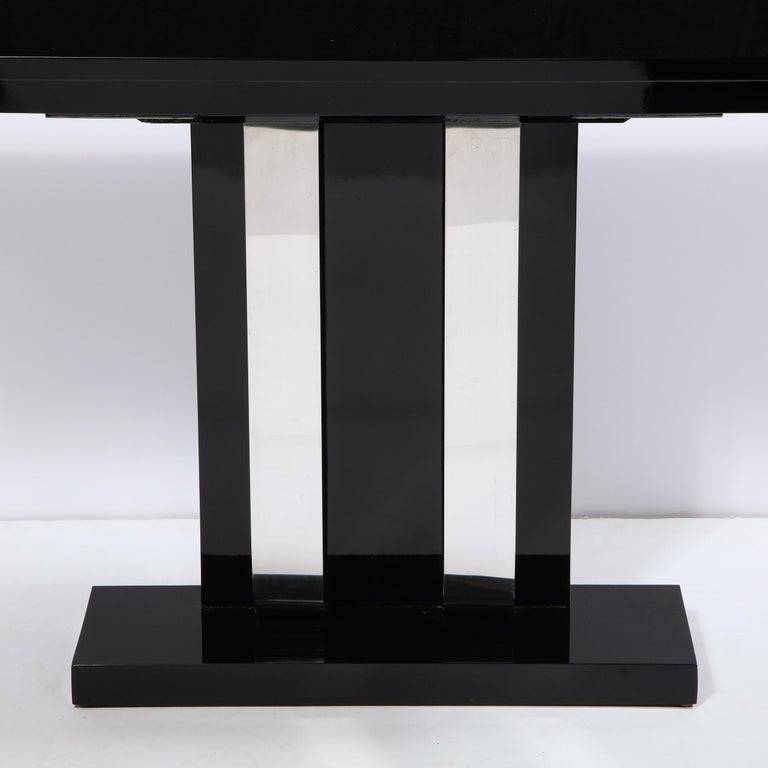 This elegant and graphic pair of Art Deco Machine Age console tables were realized in the United States, circa 1935. They feature rectilinear bodies with tiered skyscraper style tops and streamlined embellishments connecting the bases to the tops in