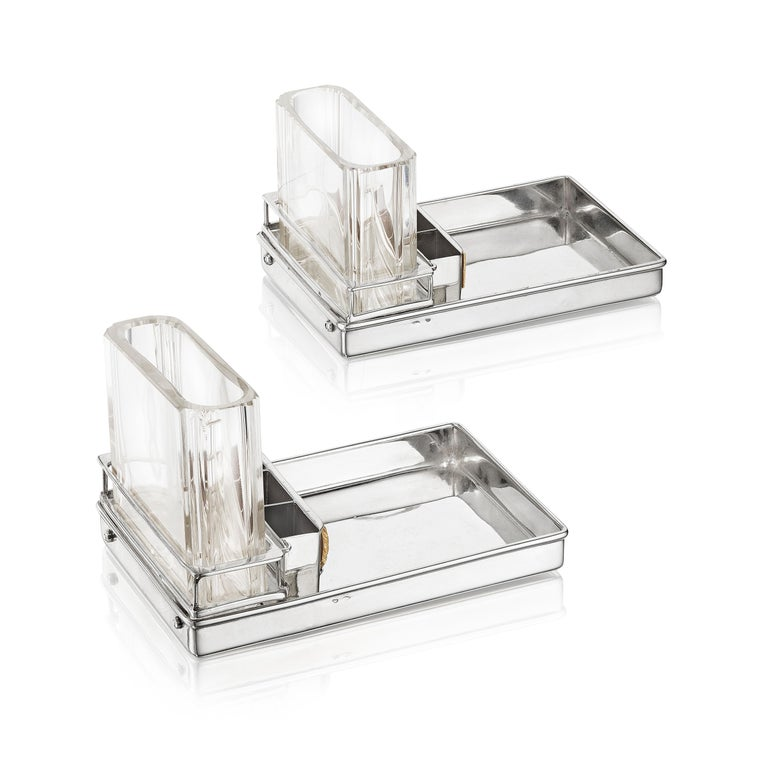 A pair of smoker's compendiums each composed of a sterling silver ashtray with compartments for matches behind a ribbed striker, the glass compartment for cigarettes; sterling silver with French marks, each signed Cartier  The 1920s and 1930s were a