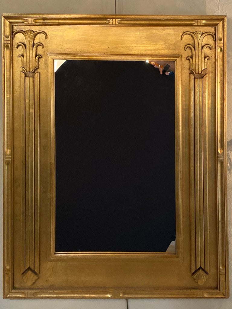 Pair of Art Deco style gilt gold architecturally carved wall or console mirrors. These solid giltwood wall, console or over the mantle mirrors are simply stunning with their sleek and stylishly carved architectural influenced frames. Having clean