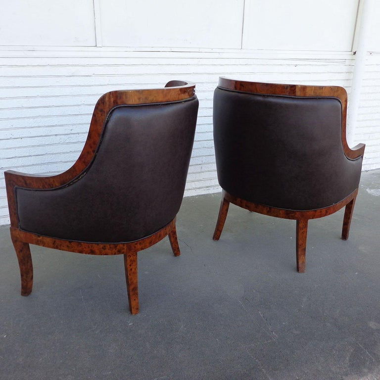 Pair of Art Deco style lounge chairs  Burl framed lounge chairs upholstered in a rich eggplant fabric.  Measures: 31.25? Width x 29.5? Depth x 43? Height Seat Height 20? Arm height 27?.