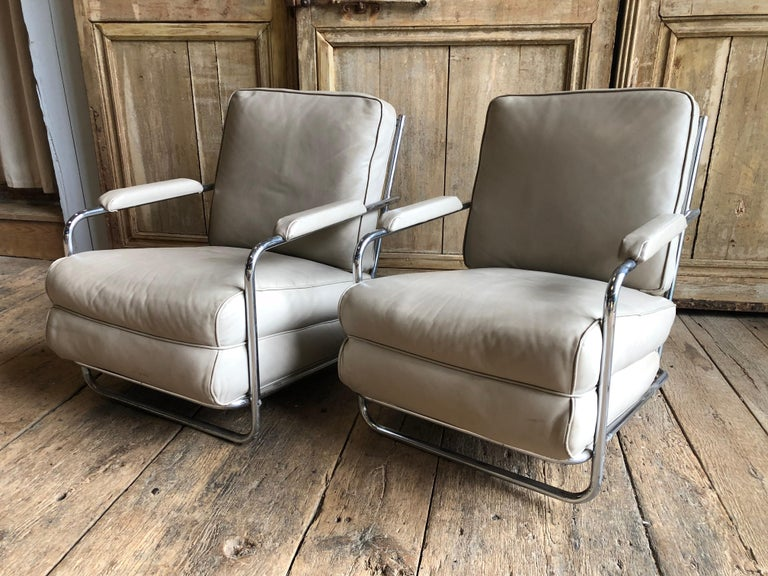 A pair of Art Deco Style chromed tubular steel framed lounge chairs with cream colored leather seats and backs, circa 1933 (in the Troy Sunshade Catalog 1933)