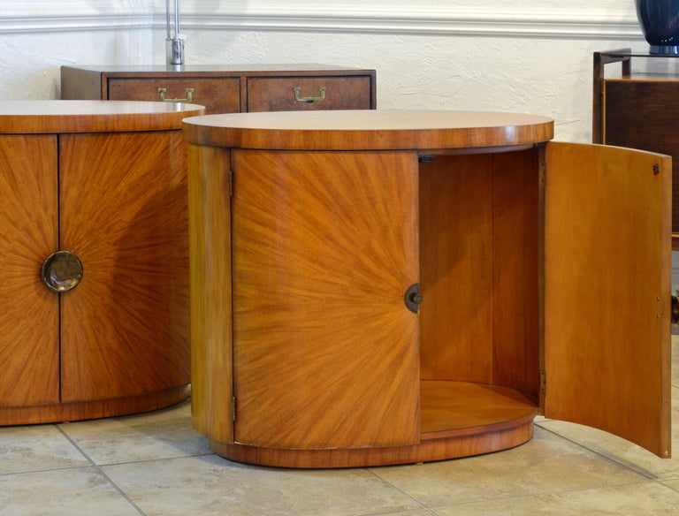 This rare pair of oval Art Deco style light mahogany cabinets or tables are finished all the way around and can be used free standing with great effect. The magnificent doors are sunburst configured and accented by hammered patinated brass handles.