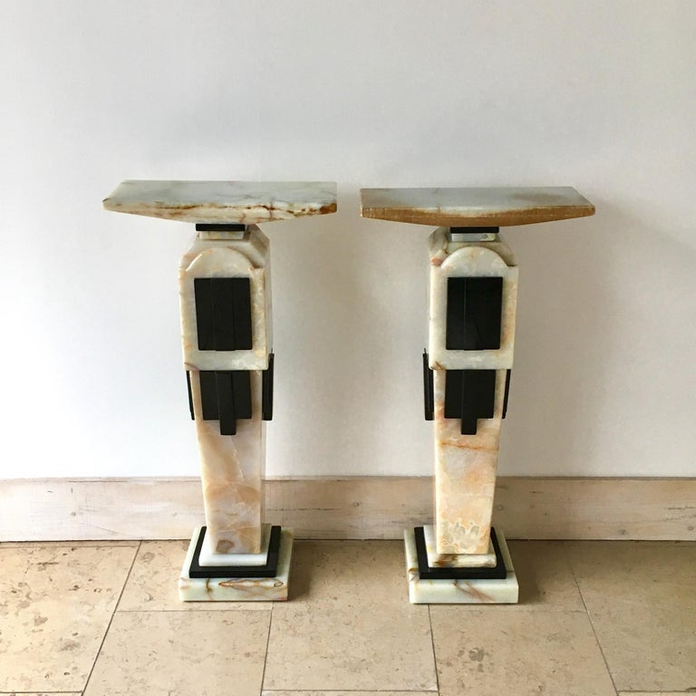 A pair of Art Deco style freestanding pedestals made from white onyx marble with polished black marble faced detail, 1980s.