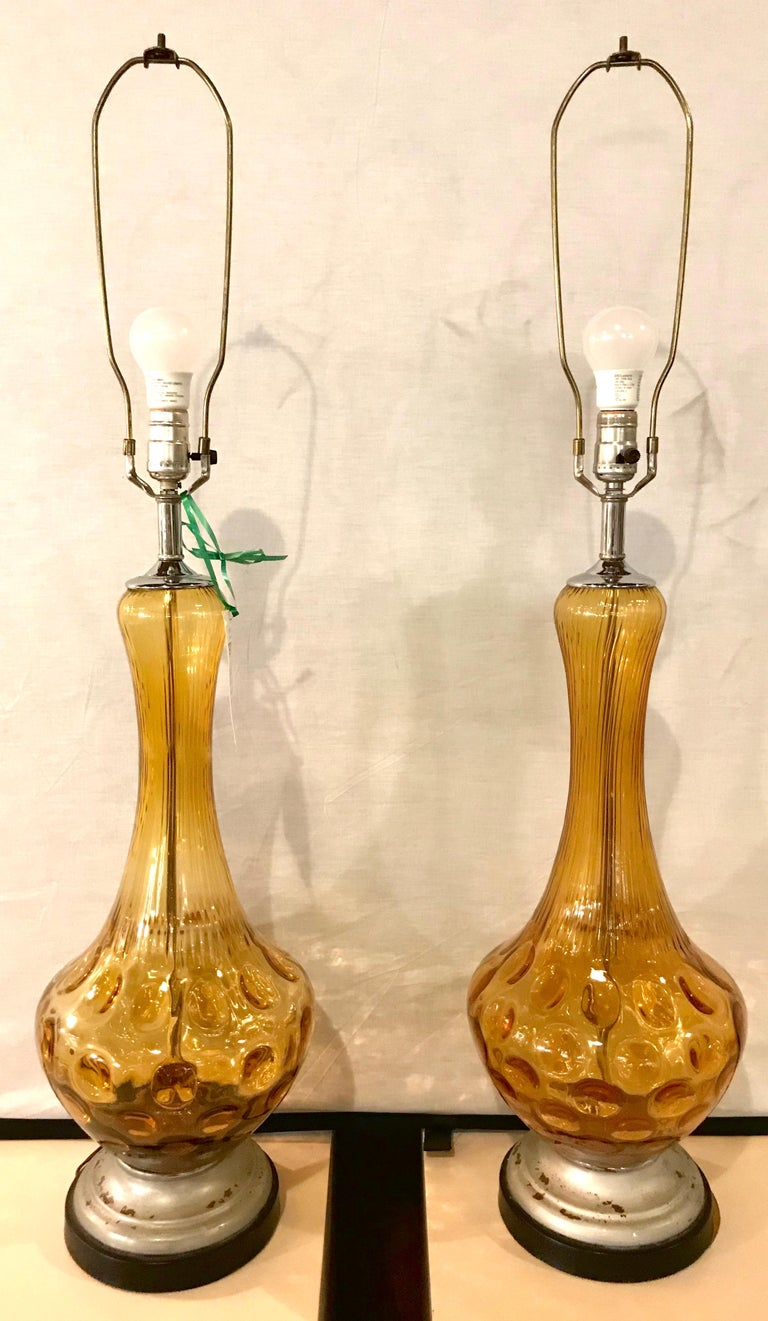Pair of Art Deco style sculpted amber glass lamps. The pair on a silver gilt and ebony wooden base.