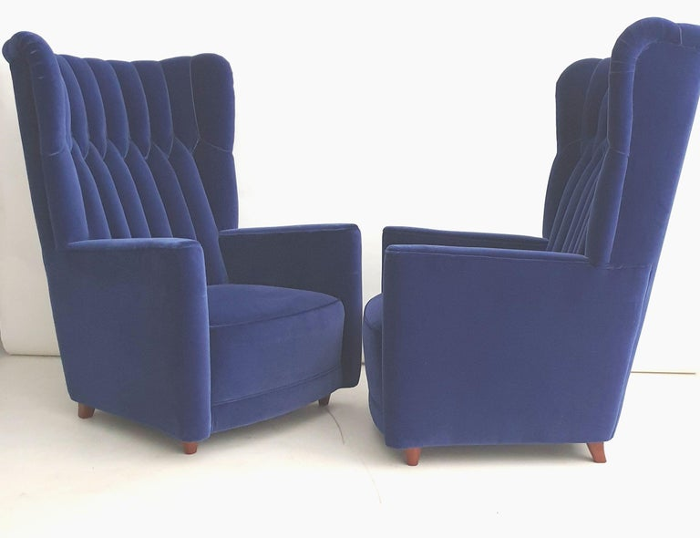 Pair of large comfortable armchairs reupholstered to match the existing vintage upholstery. The chairs have polished wooden legs and are reupholstered in a quality blue cotton velvet. Literature: L. Sacchetti, Guglielmo Ulrich, Federico Motta