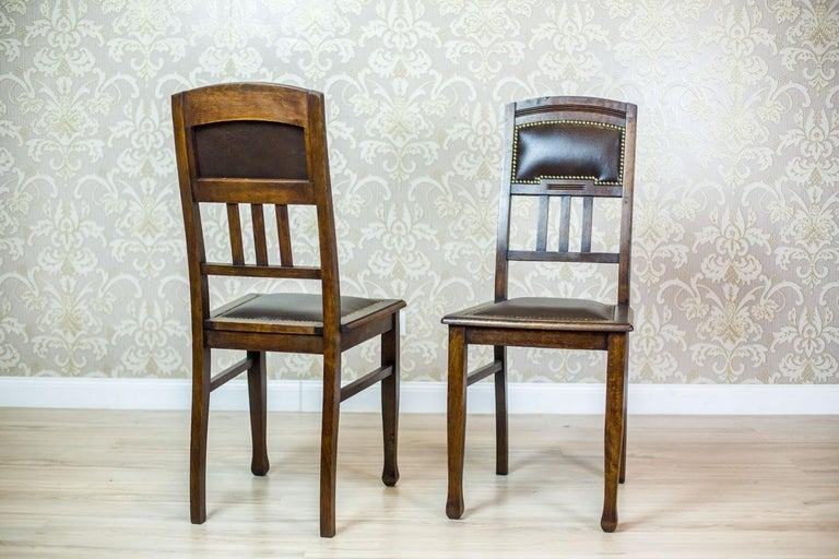 We present you two chairs made of oak wood, circa first quarter of the 20th century. The seat and the upper section of the backrest are padded with leather, which is fixed with a molding made of brass studs. These chairs are in the Art Nouveau