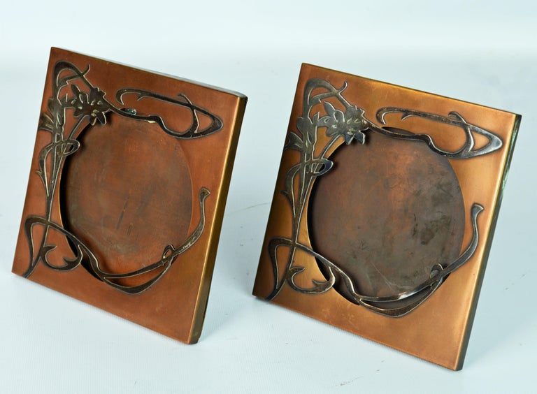 Dating to the early 20th century these exceptional art nouveau photo frames feature beautifully crafted sterling silver overlay on a patinated bronze background. Both frames are branded on the back with the Heintz logo mark.
