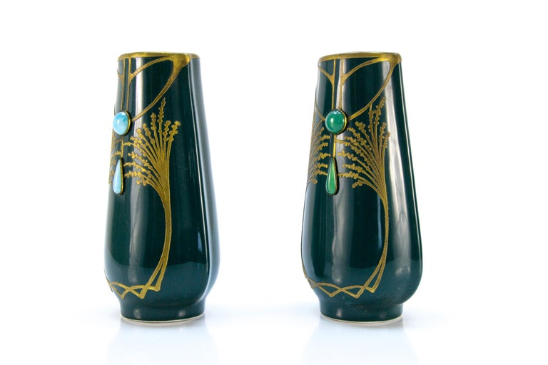 A beautiful pair of art nouveau vases decorated with blue and green glass stones, golden painting. France, early 20th century. Dimensions: Diameter of base: 5.5 cm / 2.16 in; height: 16.5 cm / 6.49 in; width 10 cm / 3.93 in x 7 cm / 2.75 in.