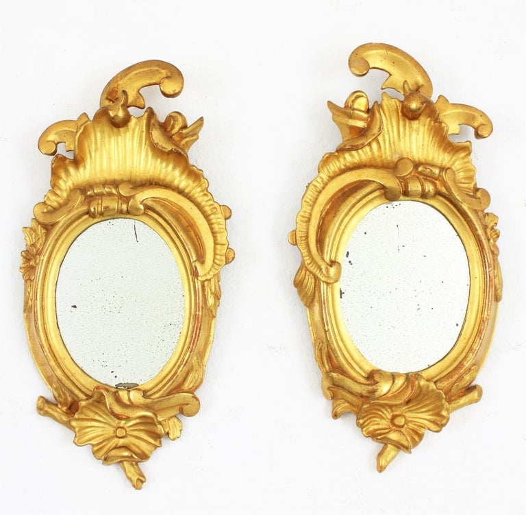Exquisite and richly carved pair of left and right petite mirrors. Carved wood, covered with gesso and 24-karat gold leaf finishing. Spain, 1910-1920s These small sized Art Nouveau carved mirrors have a naturalistic design and they are interesting