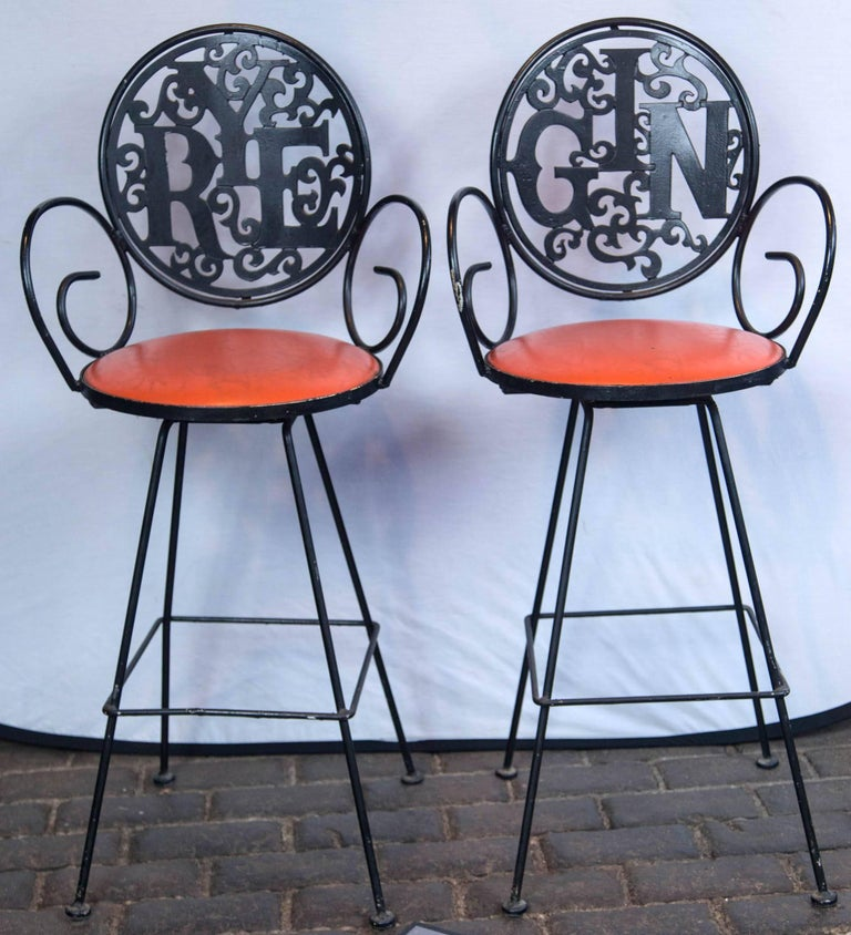 The swinging 1960s! Two 1960s wrought iron stools by Arthur Umanoff, Rye and Gin with orange vinyl seats. Seat height is 29.5 inches.