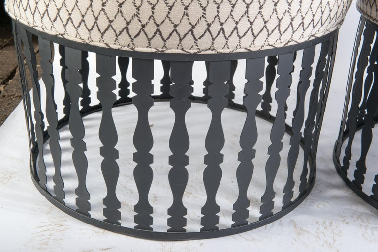 A pair of round ottomans by designer Arthur Umanoff, produced circa 1950s, composed of narrow metal cut-out baluster rails on a circular base.