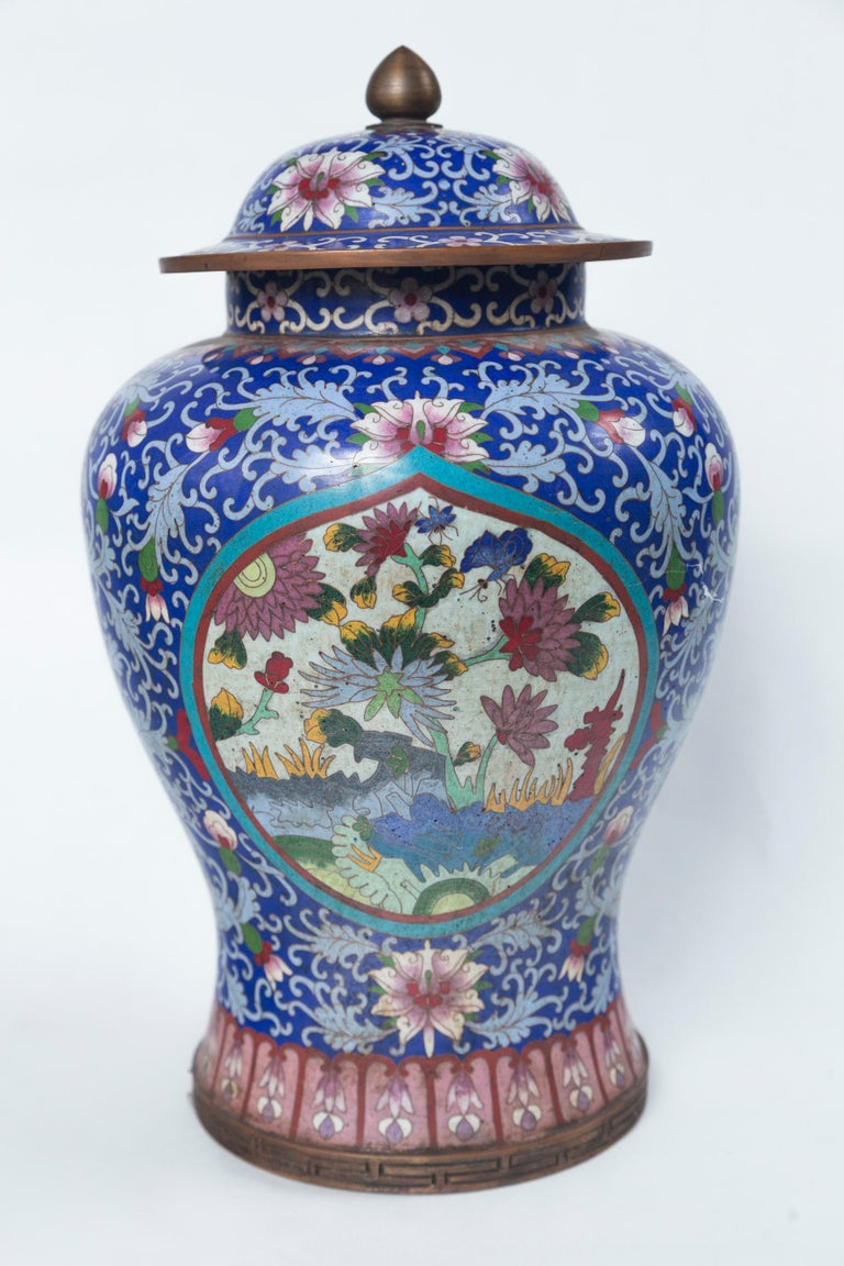 Of classical shape with blue ground. Brass finial, brass rings on lids, brass edge at base. Plaques decorated with mums and other flowers. The diameter of the base is 6.25 inches. The diameter at the widest part of the body is approximately 8 inches.