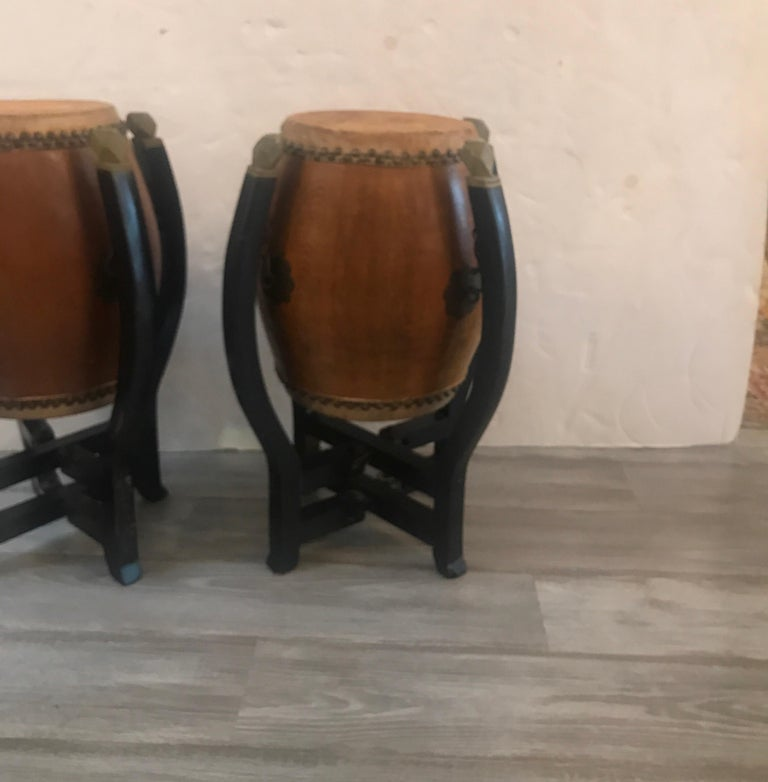 A pair of barrel shaped drums with a drum surface on the tops and bottoms with nailhead trim around the animal skins. The bases in original black paint that fold flat. Some old restoration on one leg.