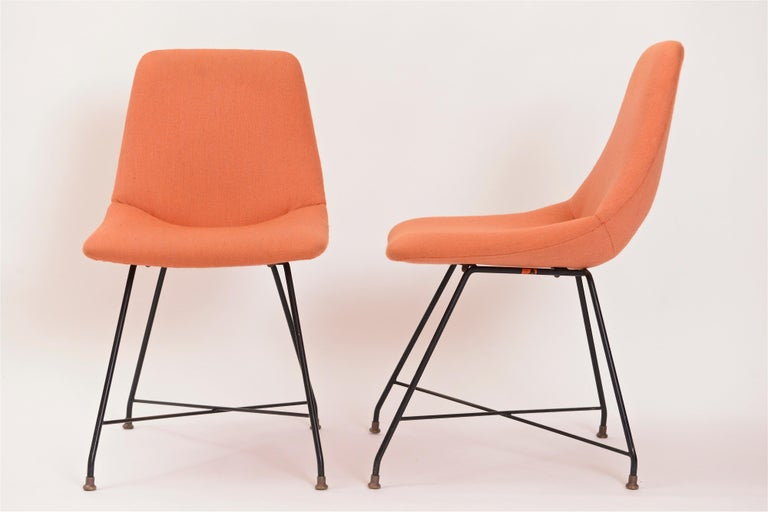 A great pair of 'Aster' chairs designed by Augusto Bozzi for Fratelli Saporiti in 1956. The chair seats, upholstered in an thick woven orange fabric, are supported by Bozzi's iconic structure of black-painted steel legs with cross stretcher and