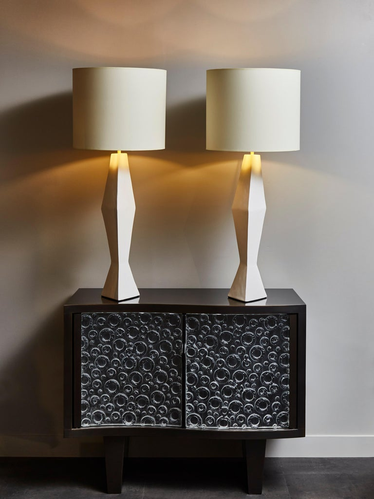 Pair of tall asymetrical table lamps made of plaster with brass settings.  Contemporary work made in France.