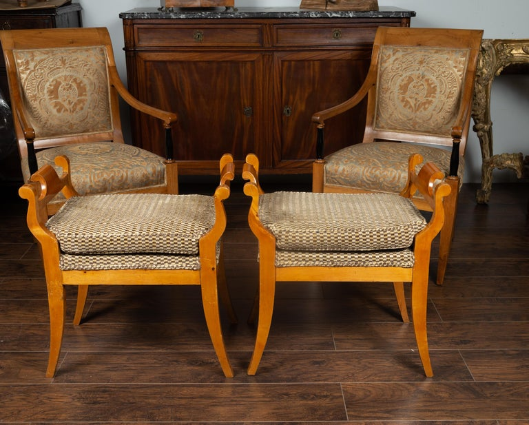 A pair of Austrian Biedermeier style wooden benches from the late 19th century, with scrolling supports, saber legs and upholstery. Born in Austria during the later years of the 19th century, each of these Biedermeier benches draws us in with its