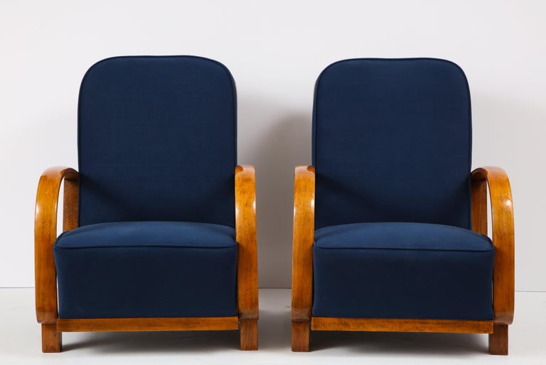 Pair of large and very comfortable Austrian Art Deco fruit-wood armchairs; the sloped wood arms beautifully shaped and extend to form the molded side, with curved wood back rest and shaped structural base support. Newly upholstered in a rich blue