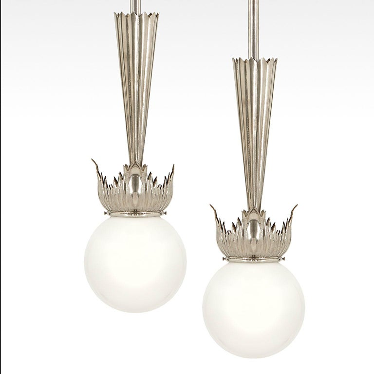 These excellent and elegant pair of Austrian Art Deco Pendant lamps have been designed by school of Dagobert Peche in Vienna, around 1925.  They feature excellent handcrafted nickel plated brass parts with opaline glass ball shades.   At the