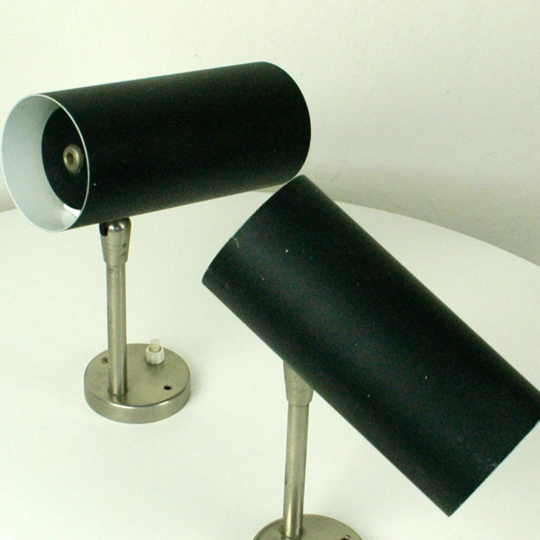 Pure and modernist, 1960s wall lights with black lacquered cylindrical metal shade, which can be adjusted into different positions designed by J. T. Kalmar Vienna. Both lamps with old original manufacturers label-.