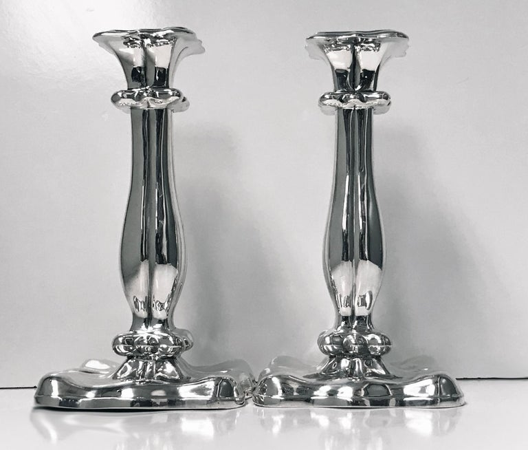 Pair of 19th century Austrian silver candlesticks, Vienna, 1840. Each on square lobate base, tapered baluster stems rising to conforming nozzles and drip pans. Marked under base with Austrian 13 loth mark for Vienna 1840 and maker's mark. Measures: