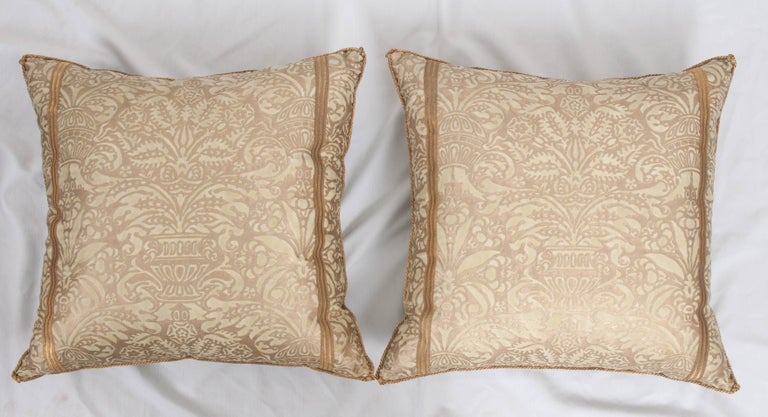Pair of Campanelle Fortuny pillows in sea-foam green and gold, with two strips of antique gold metallic military trim and backed with pale pear-green velvet. Hand-trimmed with vintage gold metallic cording which is knotted in the corners.
