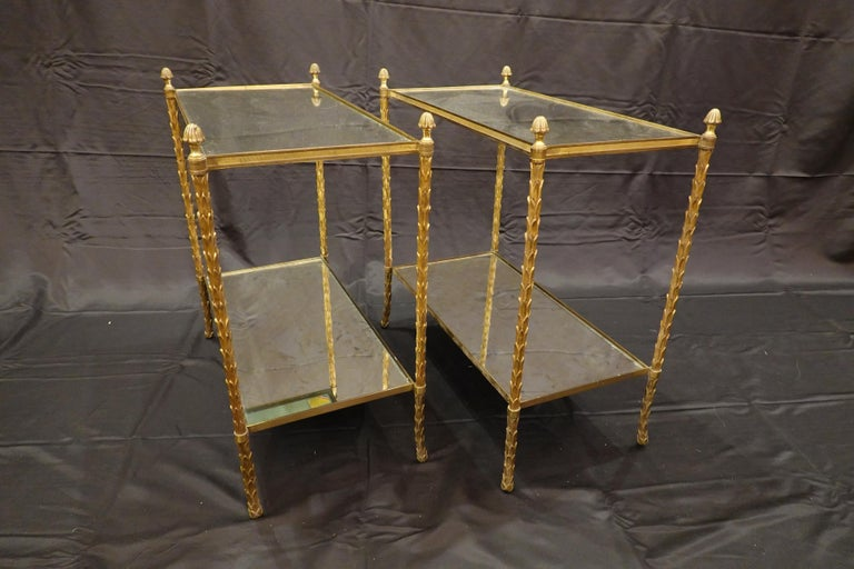 Pair of elegant gilt-bronze two-tiered side tables by French Manufacturer Maison Bagues (circa 1940s-1950s). The legs are in the form of palm fronds terminating in pine cone finials. The eglomise glass tops are slightly smokey with light gold and