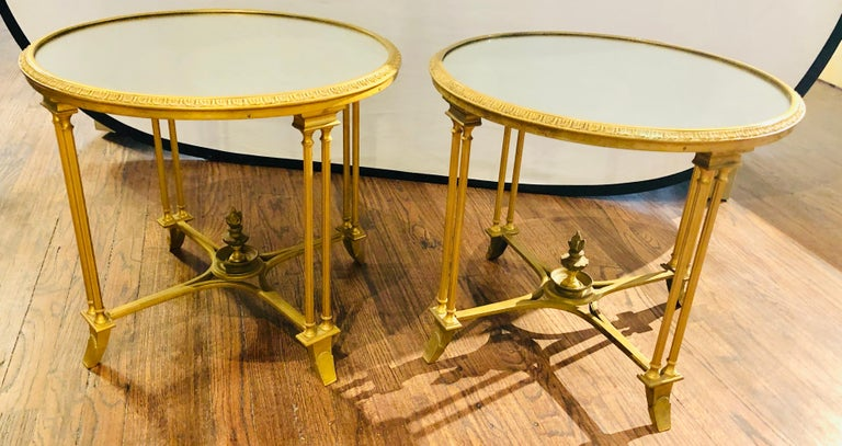 Pair of Hollywood Regency Bagues style gilt bronze neoclassical end tables or pedestals. These simply stunning end tables, pedestals or nightstands possess the finest in quality and form. The doré bronze frames having carved feet leading to double