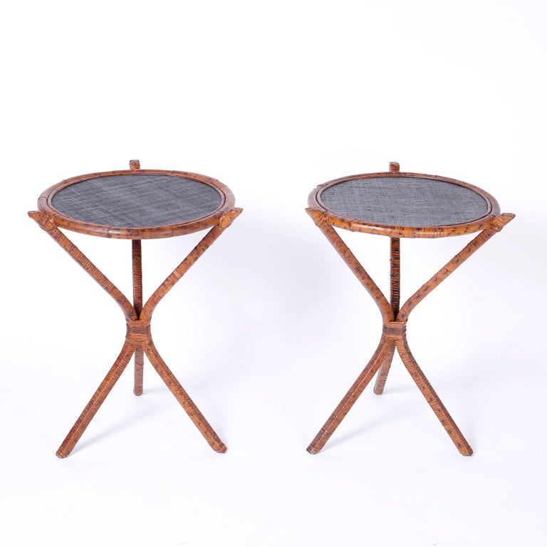 British colonial style stands with round tops framed with bent bamboo around a grasscloth surface. The bases are reed or wicker wrapped around a metal frame with a faux burnt bamboo finish. We have another pair of these tables, if 4 is required.