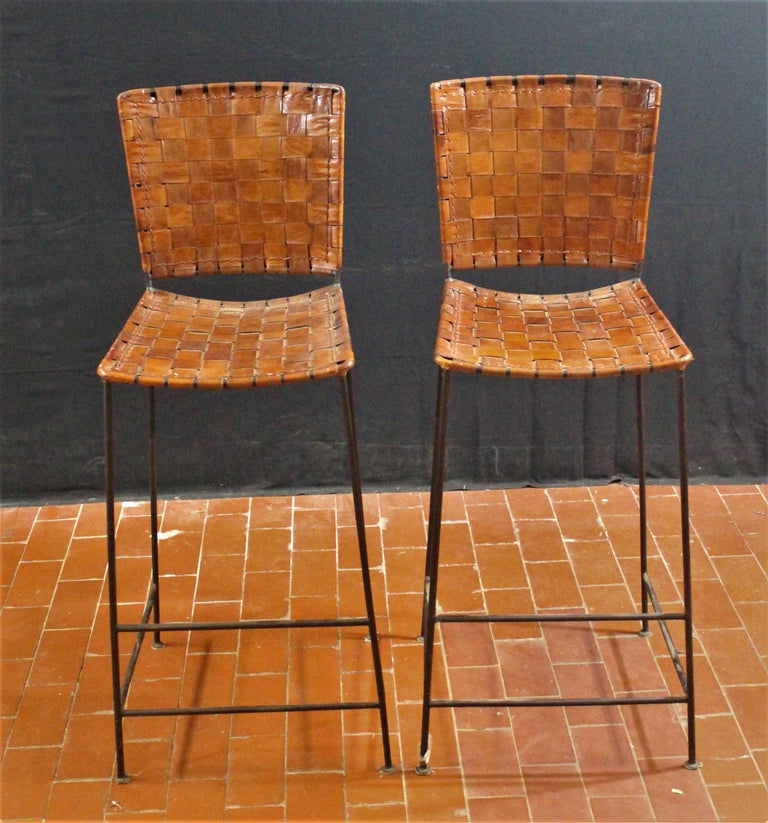 Pair of bar stools in woven saddle brown leather.