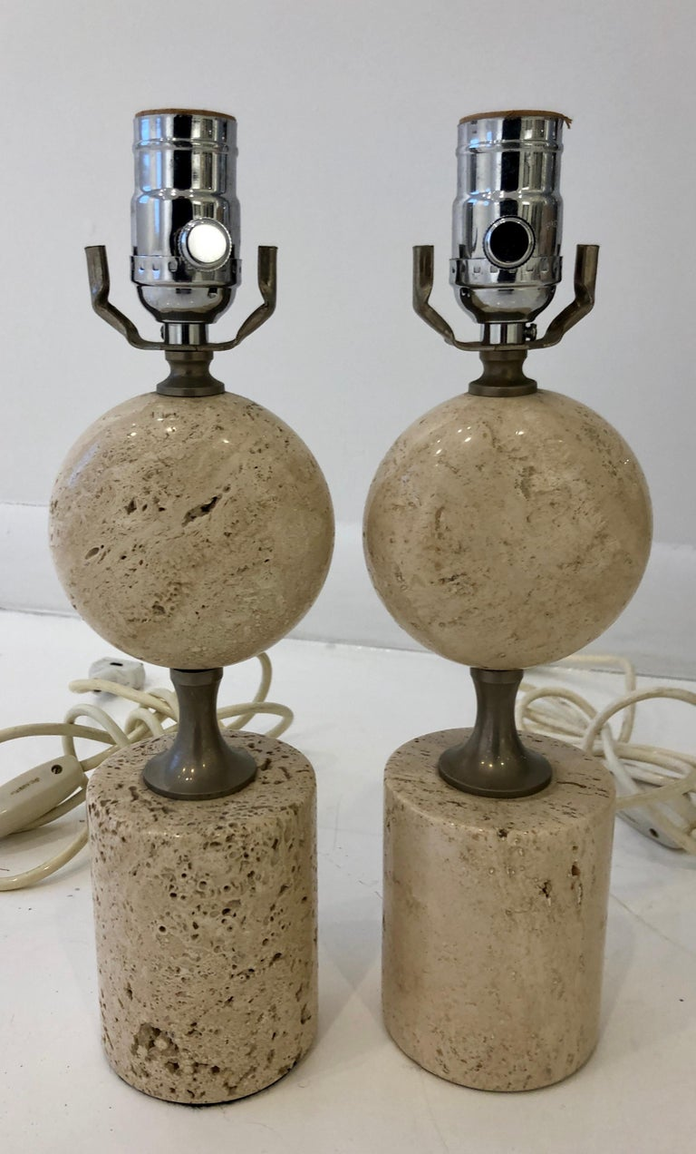 Flattened travertine orb on cylindrical travertine pedestal with solid nickel hardware.   Lamps are 13 in. to top of socket, 10 in. to top of marble.