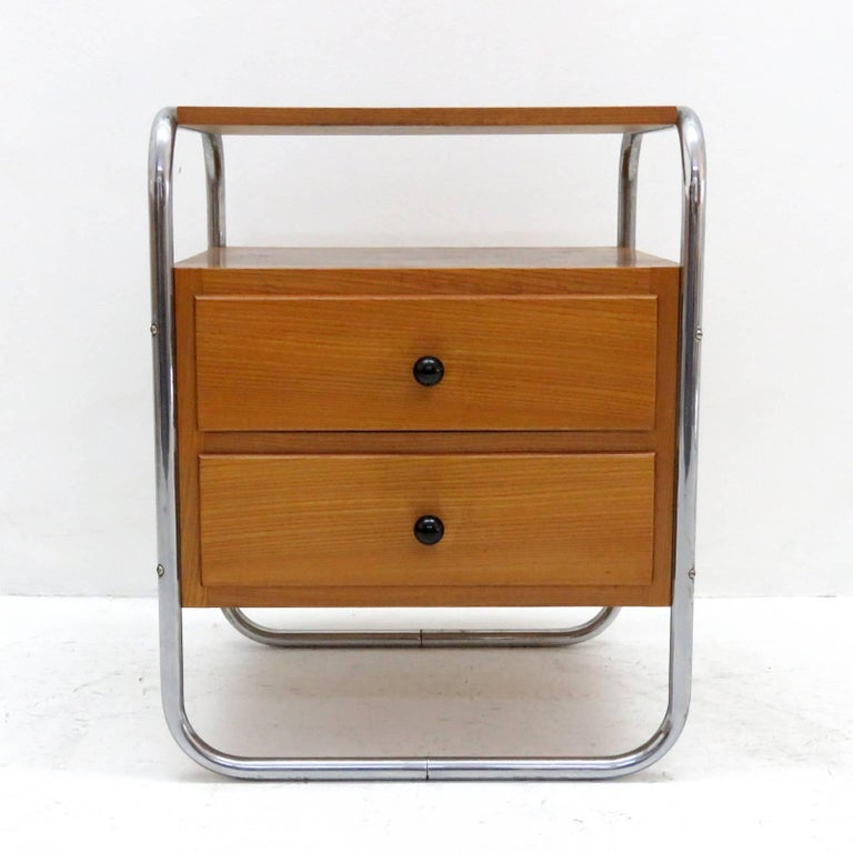 Wonderful pair of Bauhaus era bedside tables in veneered elm, each with two drawers and two shelves, tubular frames of chrome-plated metal.