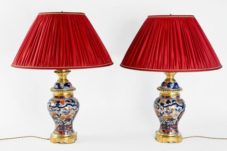Pair of vase shape lamps in Bayeux porcelain with an Imari decoration on a chiselled and gilt bronze mount. Circular base adorned with guilloche background cartouches and with four projections adorned with rosettes. Body of the lamp with a white