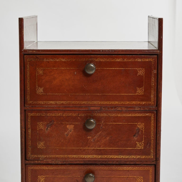 A pair of bedside tables in leather, originating in France, circa 1910.