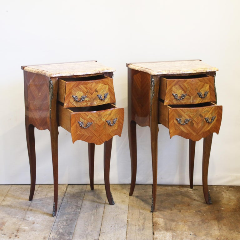 An elegant pair of matching bedside tables with marble tops. These bedside tables have two working drawers and are finished with decorative fruitwood inlay work. These bedside table are part of a set with code D1 and code D2 in our 'other furniture'