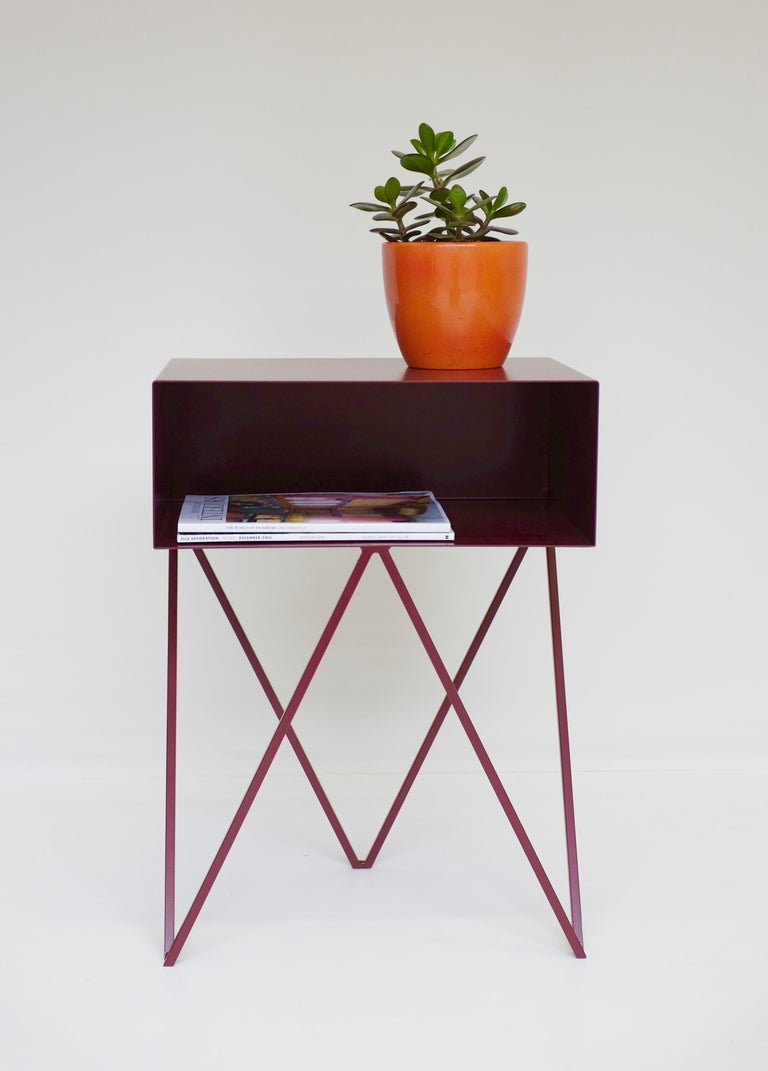 A pair of burgundy powder-coated steel robot bedside tables. The Robot side table features an open shelf on zig zag legs. A fun and functional design made of solid steel, powder coated in blueberry. The clean lines look great against period details